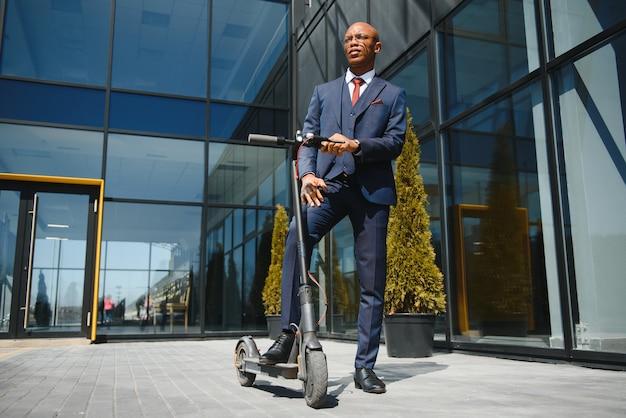 Uomo d'affari con scooter elettrico in piedi davanti al moderno edificio aziendale parlando al telefono.