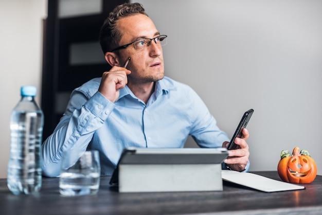 Uomo d'affari con gli occhiali che lavora dalla casa.