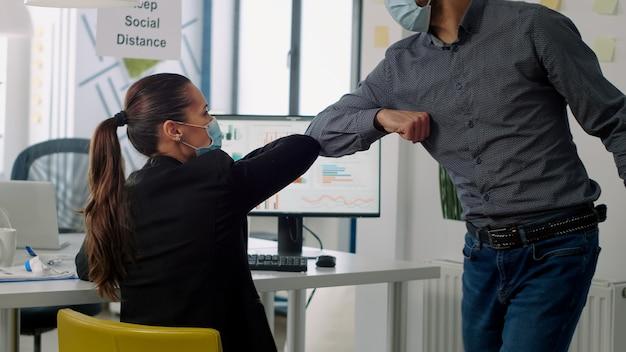 Uomo d'affari con maschera facciale che tocca il gomito per salutare il suo collega mentre lavora al progetto di comunicazione in ufficio commerciale. colleghi che rispettano il distanziamento sociale durante la pandemia globale di coronavirus