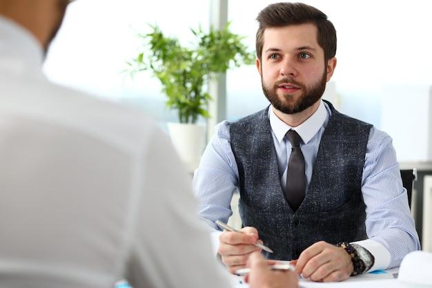 Uomo d'affari con grafico finanziario e penna d'argento in braccio risolve e discute il problema con il collega