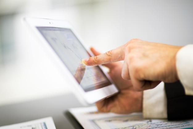 Uomo d'affari con il dito che tocca lo schermo di una tavoletta digitale