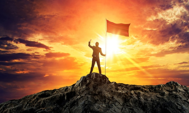 Uomo d'affari con bandiera sulla cima della montagna