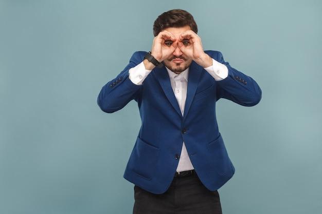 Uomo d'affari con la faccia buffa che guarda lontano con il binocolo