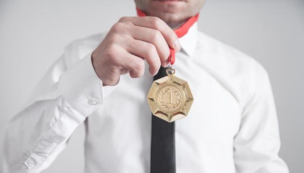 Uomo d'affari con medaglia d'oro. premi medaglia per il vincitore