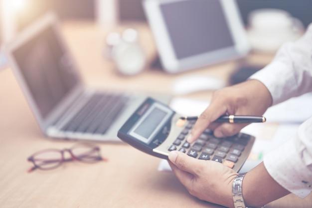 Uomo d'affari con la penna della tenuta della mano che lavora alla calcolatrice per calcolare i dati di informazioni di affari