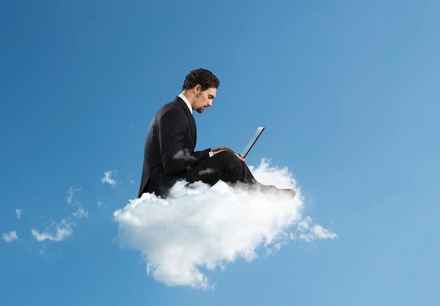 Uomo d'affari con il computer portatile su una nuvola nel cielo. internet e concetto di social network
