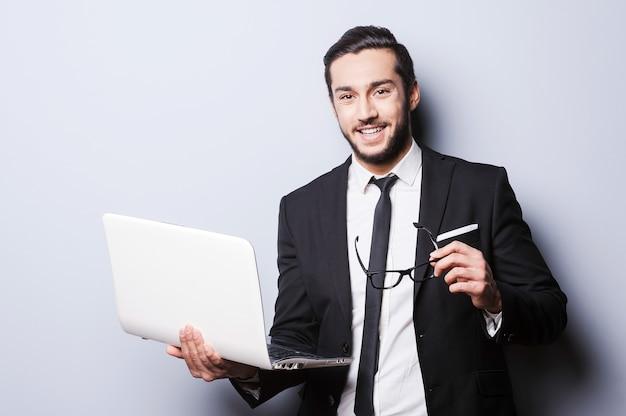 Uomo d'affari con il computer portatile. fiducioso giovane in abiti da cerimonia che tiene in mano un laptop e guarda la telecamera mentre si trova in piedi su sfondo grigio