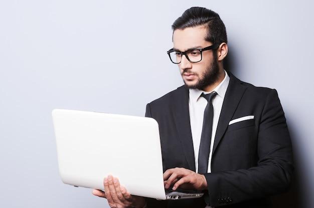 Uomo d'affari con il computer portatile. giovane fiducioso in abiti da cerimonia che lavora al computer portatile mentre si trova su uno sfondo grigio