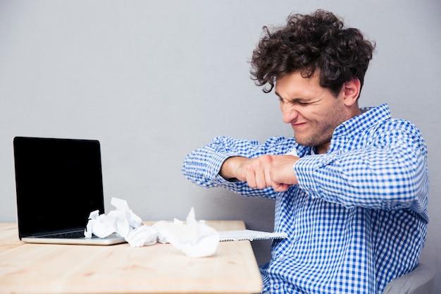 Uomo d'affari con laptop e documenti sgualciti