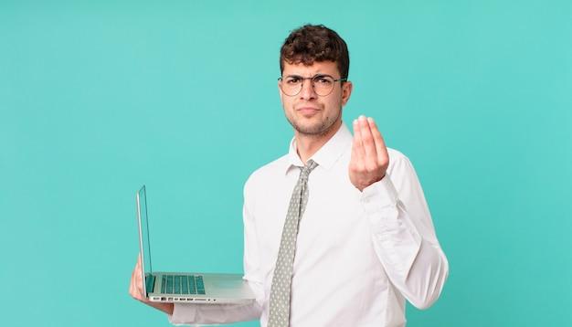 Uomo d'affari con il computer portatile che fa un gesto di denaro o di denaro, dicendoti di pagare i tuoi debiti!