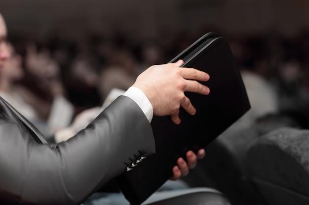 Uomo d'affari con una cartella in pelle seduto nella sala conferenze
