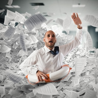 Uomo d'affari con salvagente affonda tra i fogli di lavoro in ufficio