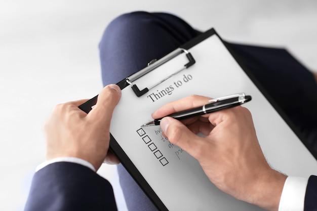 Uomo d'affari con la lista delle cose da fare in ufficio, primo piano