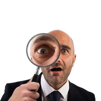 Uomo d'affari con una lente d'ingrandimento su bianco