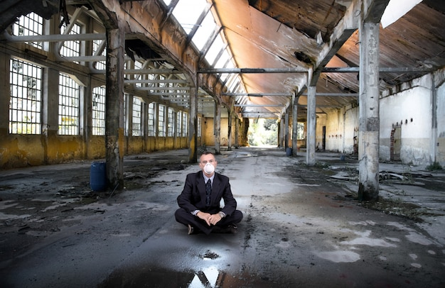 Uomo d'affari con la maschera in fabbrica abbandonata
