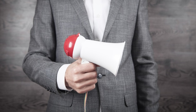 Uomo d'affari con il megafono in mano in ufficio.