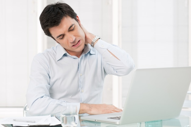 Uomo d'affari con dolore al collo dopo lunghe ore di lavoro