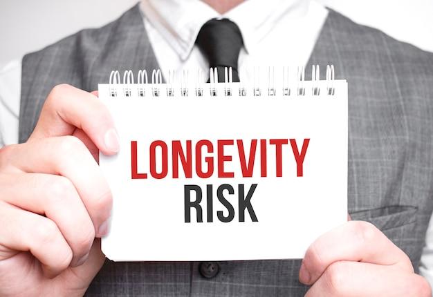 Uomo d'affari con il taccuino con testo rischio di longevità