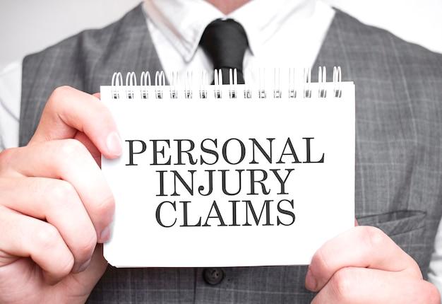 Uomo d'affari con il taccuino con il testo reclami di lesioni personali. concetto di affari