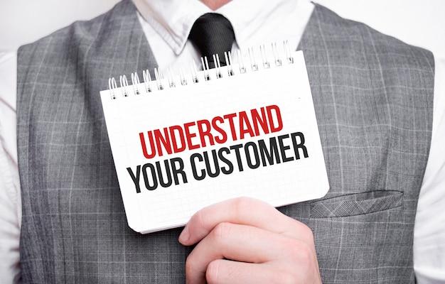 Uomo d'affari con il taccuino con testo comprendi il tuo cliente