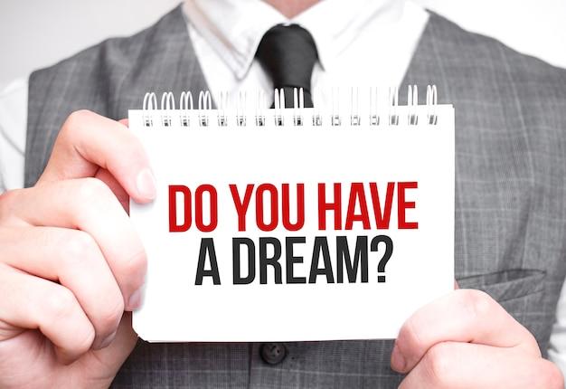 Uomo d'affari con il taccuino con testo hai un sogno