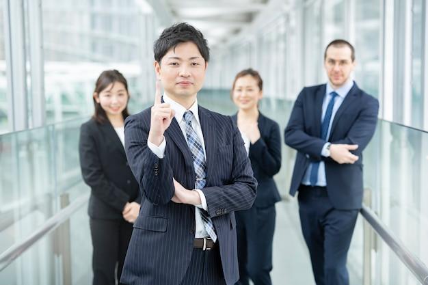 Uomo d'affari con la posa numero uno e il suo team aziendale