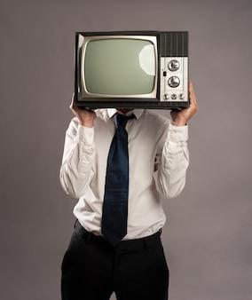 Uomo d'affari con la vecchia televisione retrò in testa