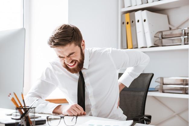 Uomo d'affari con sentimenti dolorosi trattenendo la schiena.
