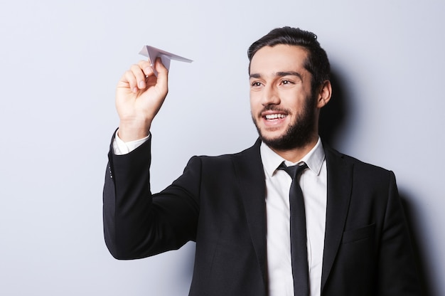 Uomo d'affari con aeroplano di carta. giovane allegro in abiti da cerimonia che tiene in mano un aeroplano di carta e sorride mentre si trova in piedi su uno sfondo grigio