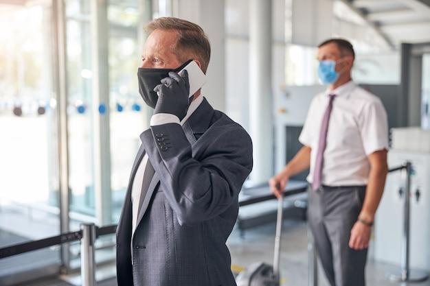 L'uomo d'affari con guanti protettivi e maschera sta parlando al cellulare mentre l'assistente trasporta i bagagli in aeroporto