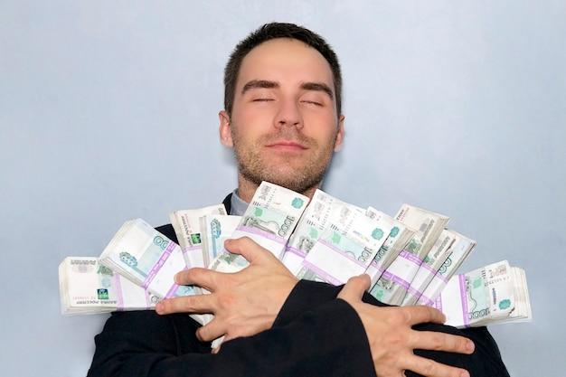 Un uomo d'affari con un'espressione soddisfatta e gli occhi chiusi del viso tiene tra le mani la somma totale di denaro in rubli russi.