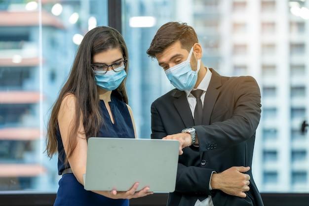 Uomo d'affari con il segretario utilizzando laptop che lavora in ufficio moderno. l'uomo e la donna discutono di lavorare insieme.