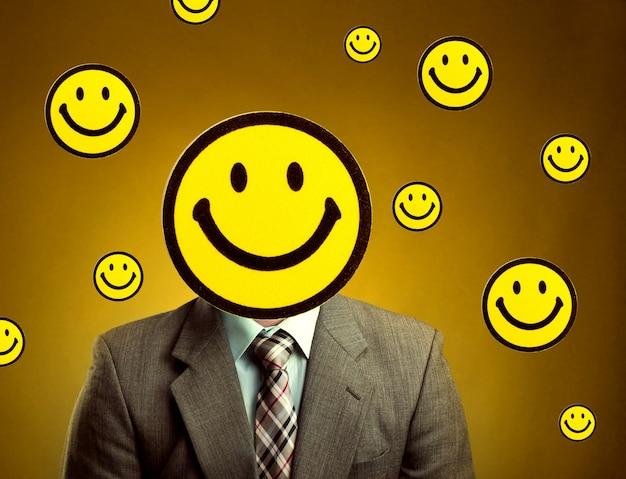 Uomo d'affari con faccina sorridente al posto della testa isolata su giallo
