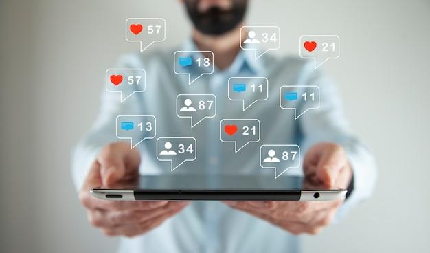 Uomo d'affari con il social media marketing sullo schermo del tablet