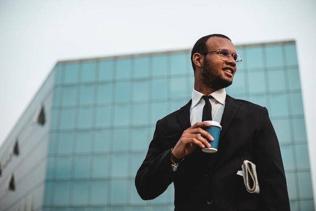 Uomo d'affari con caffè da asporto davanti al grattacielo. uomo etnico nero in giacca e cravatta