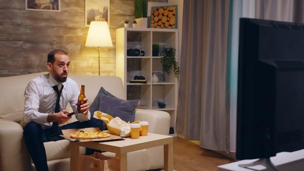 Uomo d'affari con cravatta che arriva a casa con la pizza dopo il lavoro. birra davanti alla tv.