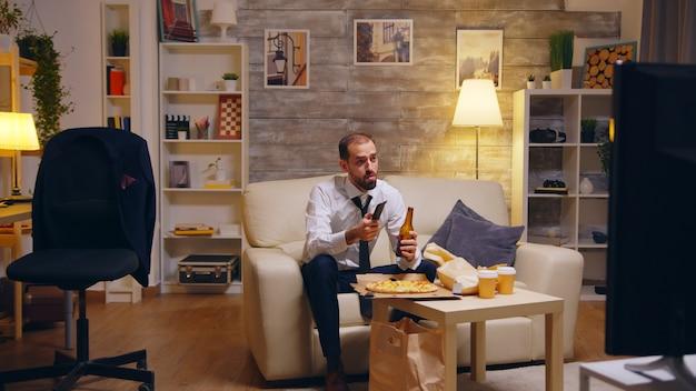 Uomo d'affari con cravatta che mangia pizza e guarda la tv dopo il lavoro. bevendo birra.