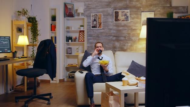 Uomo d'affari con cravatta rilassante sul divano dopo una lunga giornata di lavoro mangiando patatine e guardando la tv.