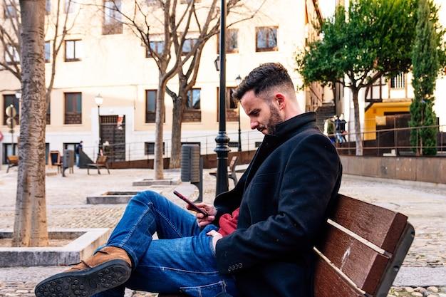 Uomo d'affari con la barba tagliata seduto su una panchina della città. usando il suo telefono cellulare.