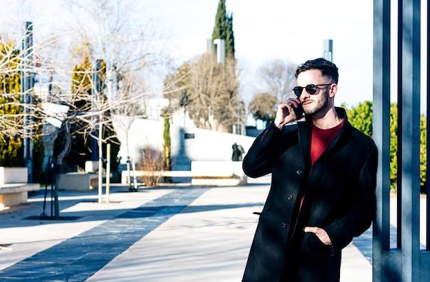 Uomo d'affari con la barba tagliata che parla con il suo telefono cellulare in uno spazio urbano. abito con lungo cappotto nero e occhiali da sole. appoggiato a una colonna della città.