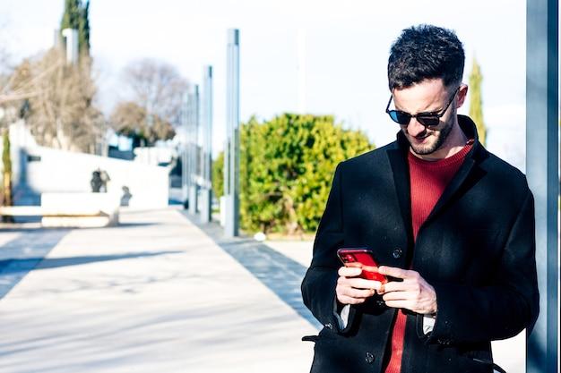 Uomo d'affari con la barba tagliata utilizzando il suo telefono cellulare in uno spazio urbano. abito con lungo cappotto nero e occhiali da sole. appoggiato a una colonna della città.