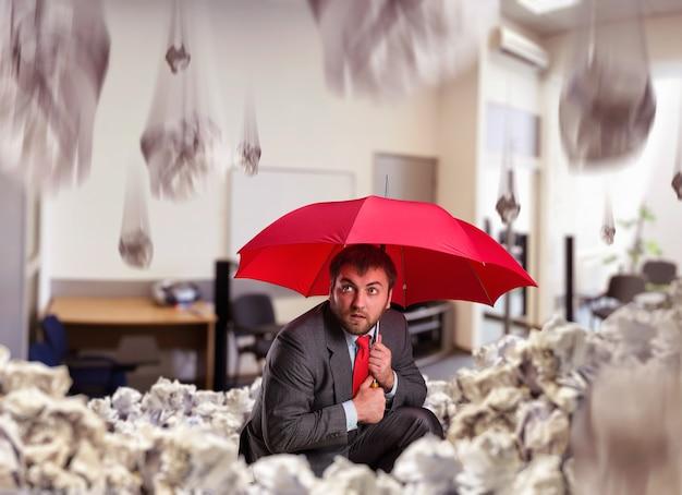 Uomo d'affari con l'ombrello in ufficio