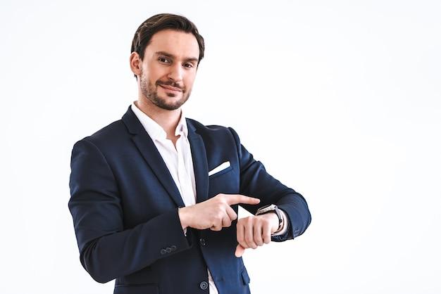 L'uomo d'affari con un orologio in piedi sullo sfondo bianco