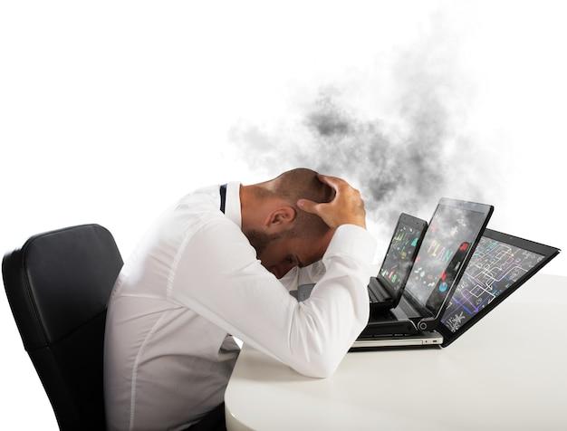 Uomo d'affari con espressione preoccupata con i computer in fumo