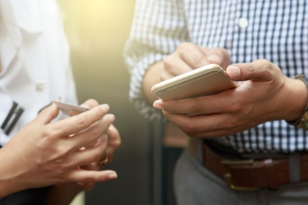 Uomo d'affari e donna discutendo su informazioni aziendali sul telefono e lo scambio di contatti
