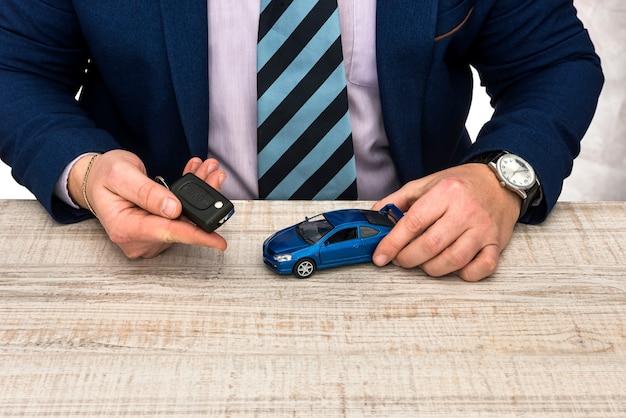 Uomo d'affari lavora in ufficio auto giocattolo e chiavi vendita o noleggio auto concept