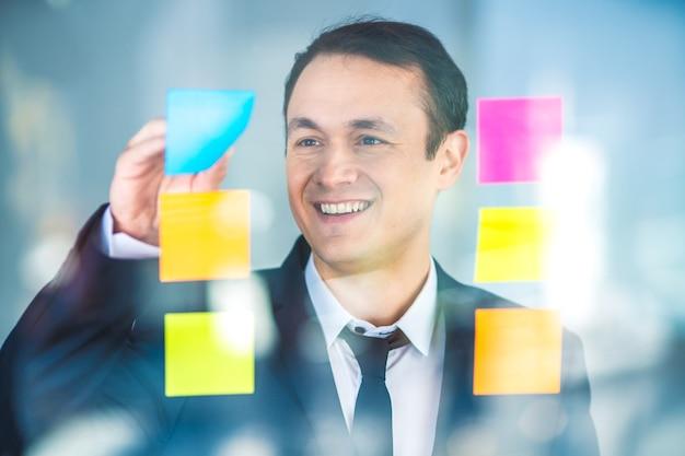 L'uomo d'affari lavora con adesivi sul vetro