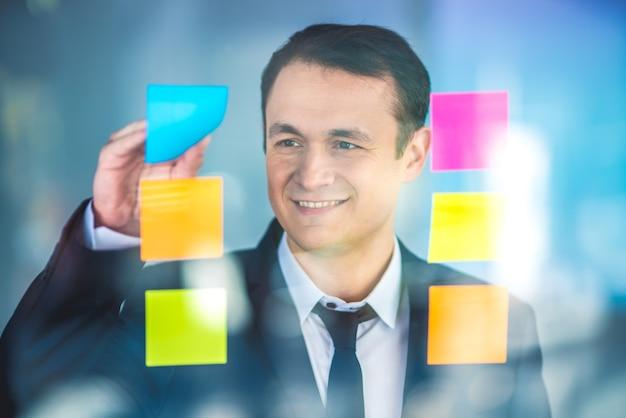 L'uomo d'affari lavora con gli adesivi sulla finestra