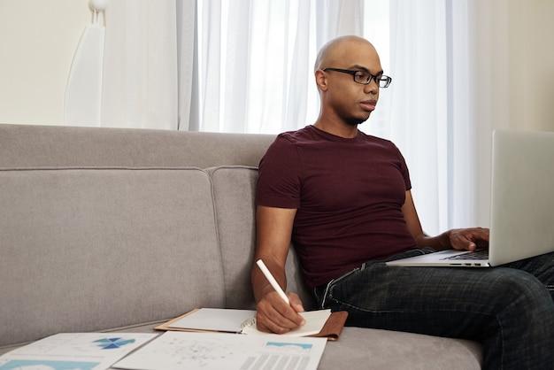 Uomo d'affari che lavora da casa a causa della pandemia, legge la posta elettronica dal cliente e prende appunti nel pianificatore