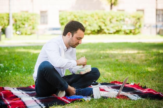 Uomo d'affari che lavora nel giardino e che mangia pranzo